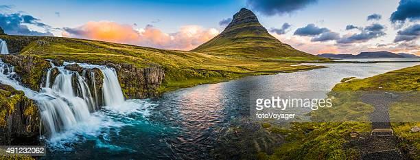 Idyllic waterfall sunrise cloudscape beside mountain peak panorama Kirkjufell Iceland
