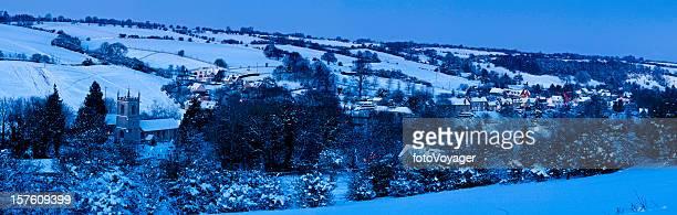 Idyllic winter village church cottages snow covered landscape Cotswolds UK
