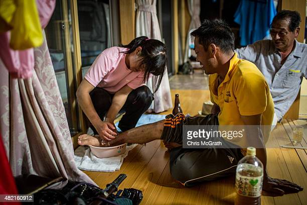 Ienobu Abe a Samurai for 18 years has his ankle iced by his daughter Rina after the days racing at the Soma Nomaoi festival on July 26 2015 in...