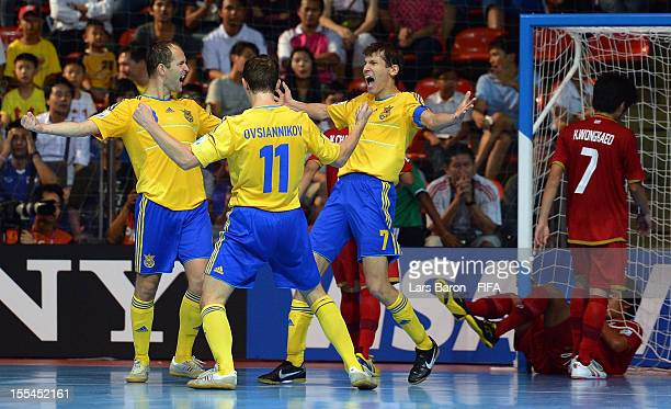 Ievgen Rogachov of Ukraine celebrates with team mates Denys Ovsiannikov and Maksym Pavlenko during the FIFA Futsal World Cup Group A match between...