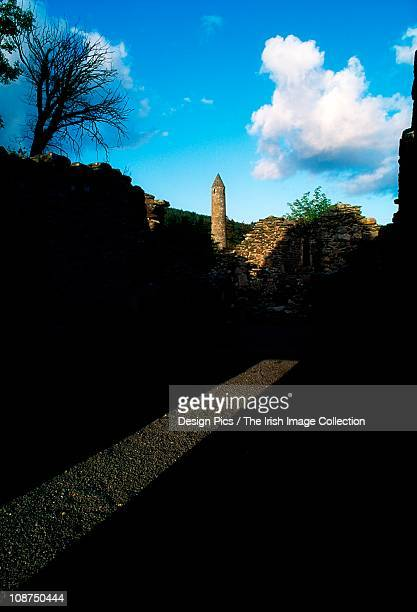 iew of round tower and ruins - irish round tower stock photos and pictures