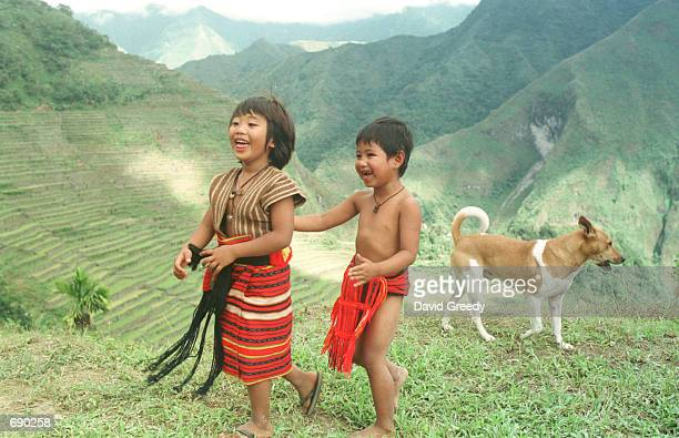 Ifugao children dressed in traditional clothing enjoy a moment before the arrival of Philippino President Gloria Macapagal Arroyo January 1 2002 to...