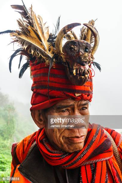 Ifugao (ancient culture of wet-rice agriculturalists) man in traditional dress and warrior hat (with monkey skull), Banaue, Luzon Island, Philippines (Model Release)