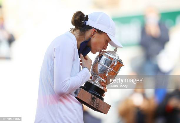 Iga Swiatek of Poland kisses the Suzanne-Lenglen cup following victory in her Women's Singles Final against Sofia Kenin of The United States of...