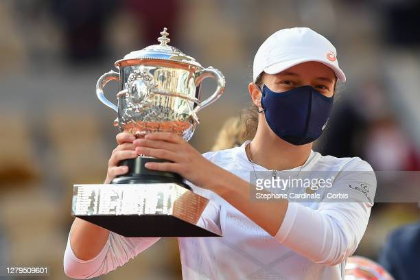 Iga Swiatek of Poland lifts the Suzanne-Lenglen cup following victory in her Women's Singles Final against Sofia Kenin of The United States of...