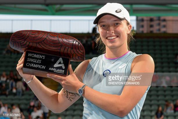 Iga Swiatek of Poland poses with the winners trophy after defeating Switzerland's Belinda Bencic in the women's singles final match at the Adelaide...