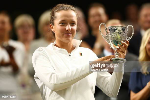 Iga Swiatek of Poland winner of the Girls' Singles final poses with her trophy in Centre Court on day twelve of the Wimbledon Lawn Tennis...