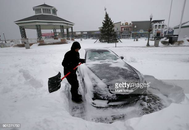 Igal Cohen shovels his parking spot in front of his storefront on January 4 2018 in Rehoboth Beach Delaware A winter storm is traveled up the east...