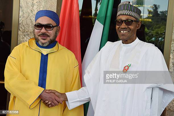 igerian President Muhammadu Buhari shakes hand with King of Morocco Mohammed VI upon his arrival at the presidential palace in Abuja on December 2...