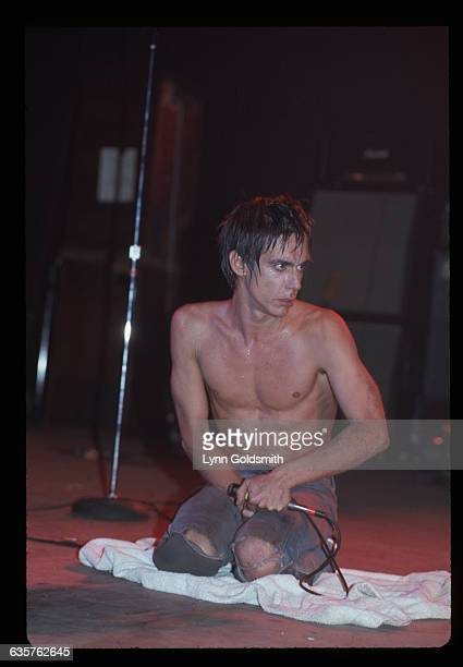 Iggy Pop is shown seated on stage performing Undated