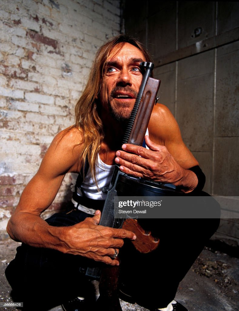 Iggy Pop poses holding a gun during a studio portrait session in Williamsburg on 21st May 2001 in New York.