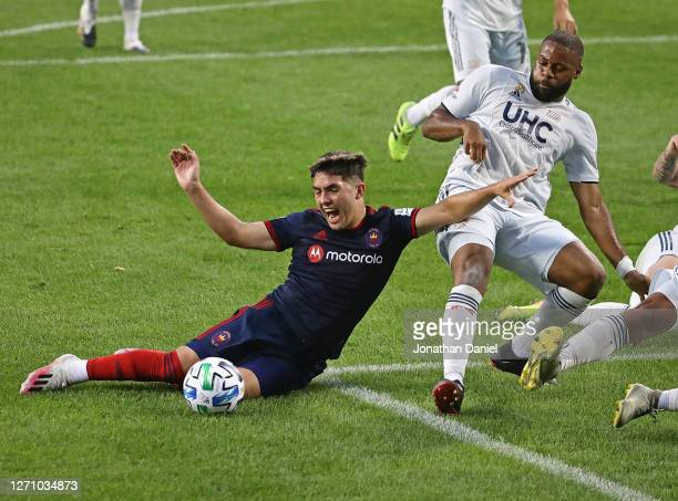 Ignacio Aliseda of Chicago Fire is knocked to the ground by Andrew Farrell of New England Revolution at Soldier Field on September 06, 2020 in...