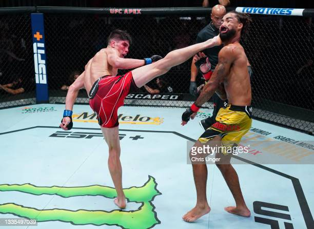 Ignacio Bahamondes of Chile knocks out Roosevelt Roberts with a kick in a lightweight fight during the UFC Fight Night event at UFC APEX on August...