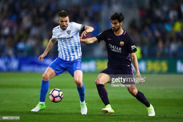 Ignacio Camacho of Malaga CF competes for the ball with Andre Gomes of FC Barcelona during the La Liga match between Malaga CF and FC Barcelona at La...