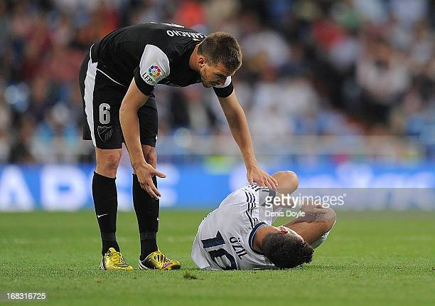 Ignacio Camacho of Malaga CF helps Mesut Ozil of Real Madrid CF after he got injured during the La Liga match between Real Madrid CF and Malaga CF at...