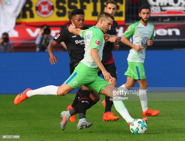 Ignacio Camacho of Wolfsburg and Leon Bailey of Leverkusen battle for the ball during the Bundesliga match between Bayer 04 Leverkusen and VfL...