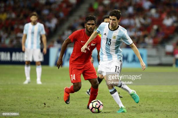 Ignacio Fernandez of Argentina dribbles past Hariss Harun of Singapore during the International Test match between Argentina and Singapore at...