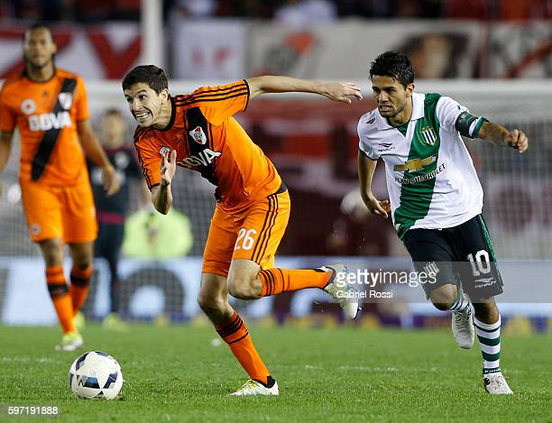 Ignacio Fernandez of River Plate drives the ball past Walter Erviti of Banfield during a match between River Plate and Banfield as part of first...