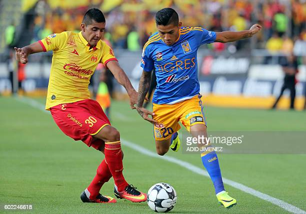 Ignacio Gonzalez of Morelia vies for the ball with Javier Aquino of Tigres during their Mexican Apertura 2016 tournament football match at the Jose...