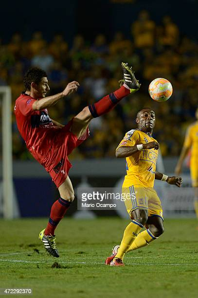 Ignacio Gonzalez of Universitario de Sucre kicks the ball as Joffre Guerron of Tigres tries to defend during a second leg match between Tigres and...