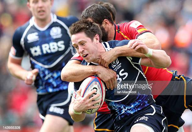 Ignacio Martin of Spain tackles John Houston of Scotland during the match between Scotland and Spain on day two of the IRB Glasgow Sevens at...