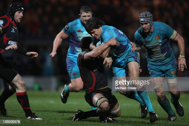 Ignacio Mieres of Exeter Chiefs is held up by Gavin Thomas of Newport Gwent Dragons during the Amlin Challenge Cup Pool Four match between Exeter...