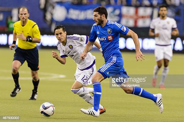 Ignacio Piatti of Montreal Impact tries to move the ball past Eric Avila of Orlando City SC during the MLS game at the Olympic Stadium on March 28...