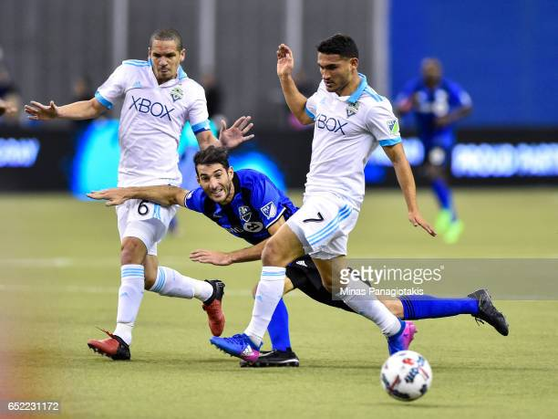Ignacio Piatti of the Montreal Impact gets caught between Osvaldo Alonso and Cristian Roldan of the Seattle Sounders during the MLS game at Olympic...