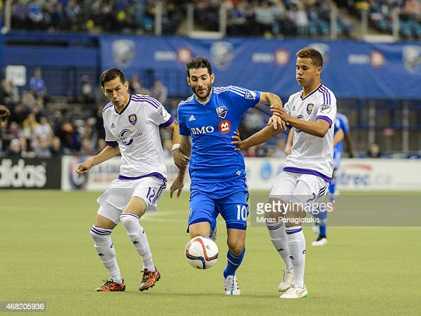 Ignacio Piatti of the Montreal Impact tries to move the ball past Eric Avila and Tyler Turner of Orlando City SC during the MLS game at the Olympic...