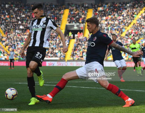 Ignacio Pussetto of Udinese Calcio competes for the ball with Evangelista Lyanco of Bologna FC during the Serie A match between Udinese and Bologna...