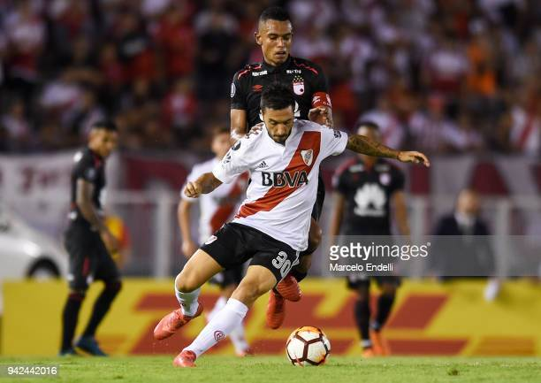 Ignacio Scocco of River Plate fights for ball with William Tesillo of Independiente Santa Fe during a Copa CONMEBOL Libertadores match between River...