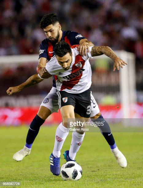 Ignacio Scocco of River Plate fights for the ball with Gabriel Gudiño of San Lorenzo during a match between River Plate and San Lorenzo as part of...