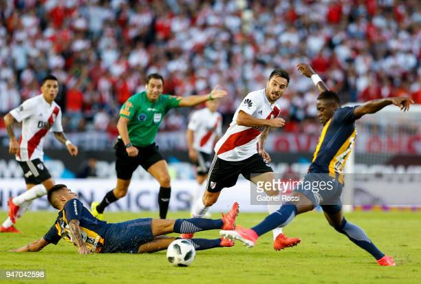 Ignacio Scocco of River Plate fights for the ball with Joaquin Pereyra and Oscar Cabezas of Rosario Central during a match between River Plate and...