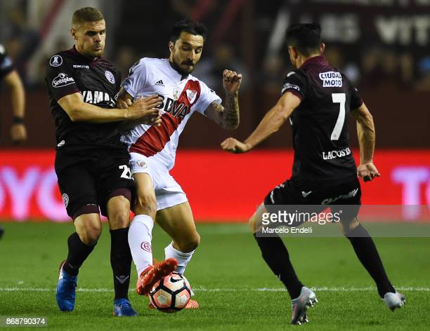 Ignacio Scocco of River Plate fights for the ball with Nicolas Pasquini and Lautaro Acosta of Lanus during a second leg match between Lanus and River...