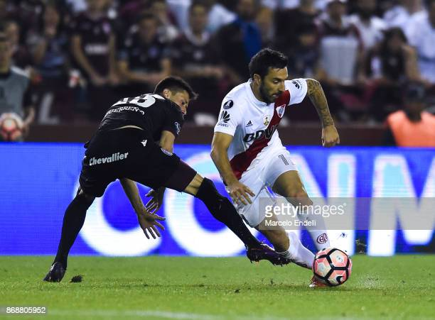 Ignacio Scocco of River Plate fights for the ball with Rolando Garcia of Lanus during a second leg match between Lanus and River Plate as part of the...