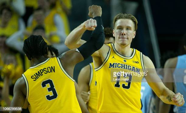 Ignas Brazdeikis and Zavier Simpson of the Michigan Wolverines celebrate a three point play during the second half of the game against the North...