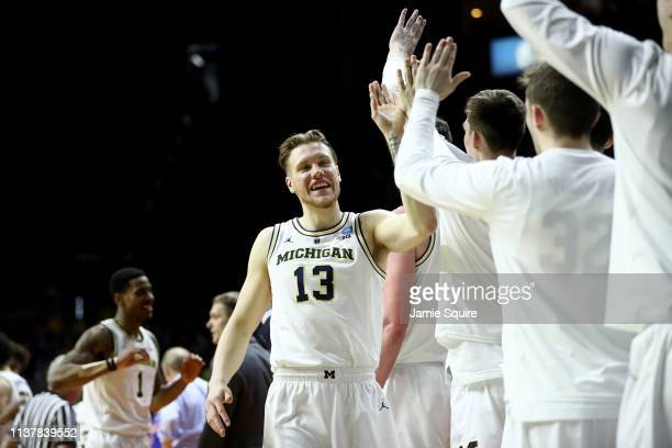 Ignas Brazdeikis of the Michigan Wolverines celebrates with his teammates against the Florida Gators during the second half in the second round game...