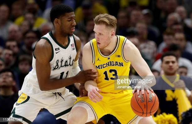 Ignas Brazdeikis of the Michigan Wolverines dribbles the ball while being guarded by Aaron Henry of the Michigan State Spartans in the second half...