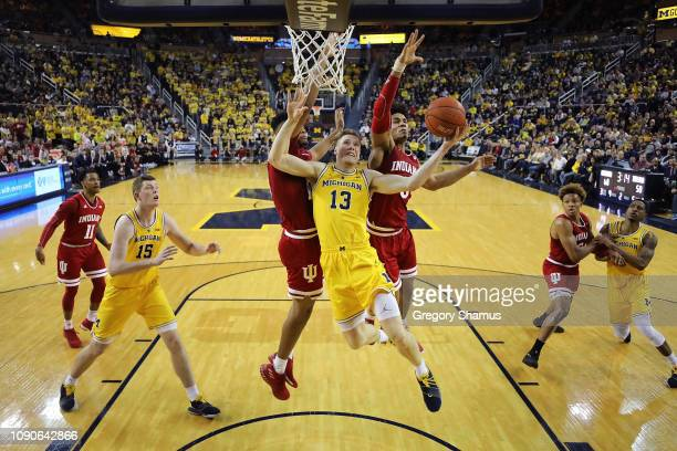 Ignas Brazdeikis of the Michigan Wolverines drives to the basket past Justin Smith and Devonte Green at Crisler Arena on January 06 2019 in Ann Arbor...