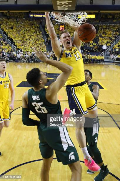 Ignas Brazdeikis of the Michigan Wolverines dunks next to Kenny Goins of the Michigan State Spartans during the second half at Crisler Arena on...
