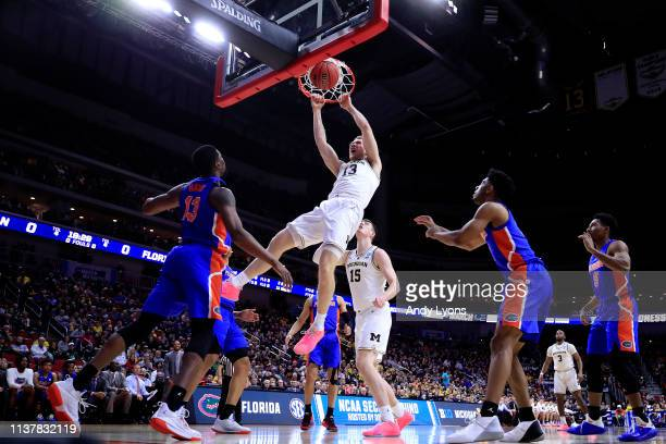 Ignas Brazdeikis of the Michigan Wolverines dunks the ball against the Florida Gators during the first half in the second round game of the 2019 NCAA...