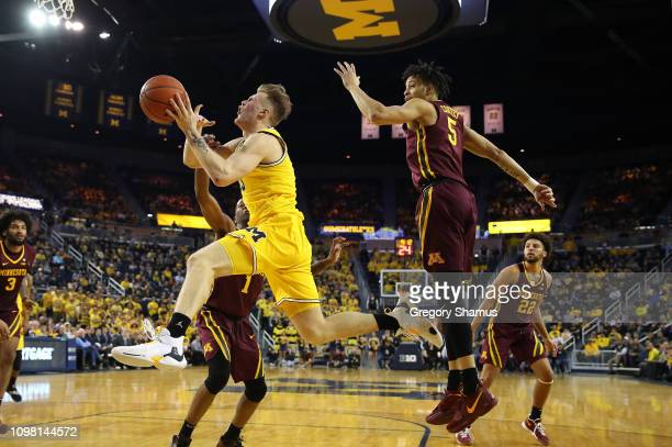 Ignas Brazdeikis of the Michigan Wolverines tries to get a shot while driving past Amir Coffey of the Minnesota Golden Gophers during the second half...