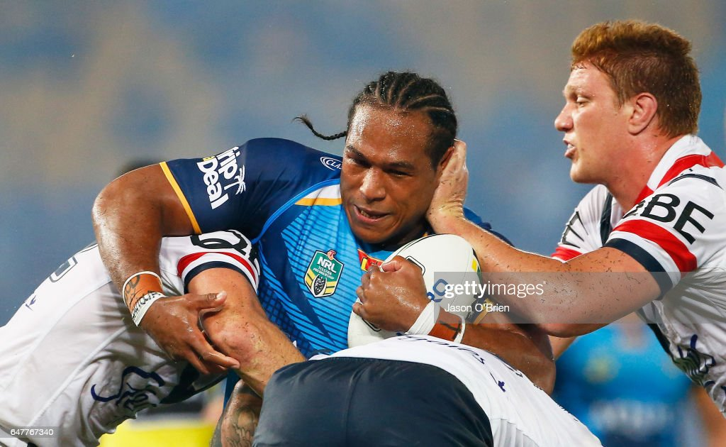 Ignattius Paasi of the Titans is tackled during the round one NRL match between the Gold Coast Titans and the Sydney Roosters at Cbus Super Stadium on March 4, 2017 in Gold Coast, Australia.