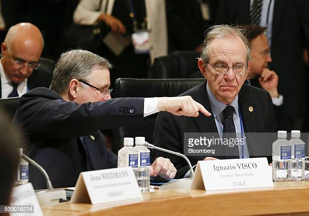 Ignazio Visco governor of the Bank of Italy left gestures as he speaks to Pier Carlo Padoan Italy's finance minister as they attend the Group of...