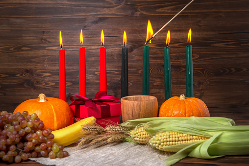 ignition of Kwanzaa traditional candles, festival concept with gift box, pumpkins, ears of wheat, grapes, corns, banana, bowl and fruits on wooden background, close up 879222838