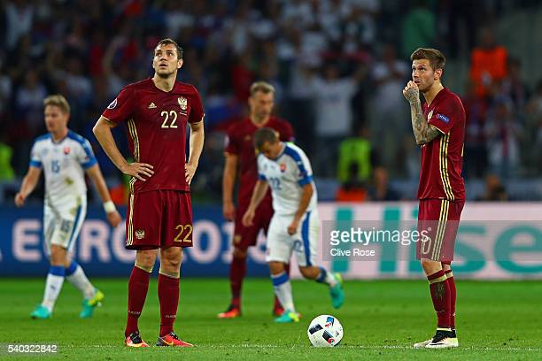 Igor Akinfeev of Russia and Artem Dzyuba of Russia look on as the Slovakian team celebrate during the UEFA EURO 2016 Group B match between Russia and...