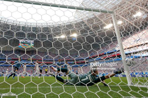 Igor Akinfeev of Russia dives but is beaten by a shot from Diego Laxalt of Uruguay for the second goal during the 2018 FIFA World Cup Russia group A...