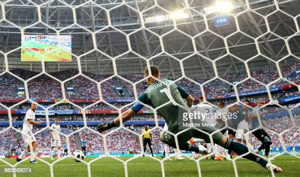 Igor Akinfeev of Russia is beaten by a freekick by Luis Suarez of Uruguay for the opening goal during the 2018 FIFA World Cup Russia group A match...
