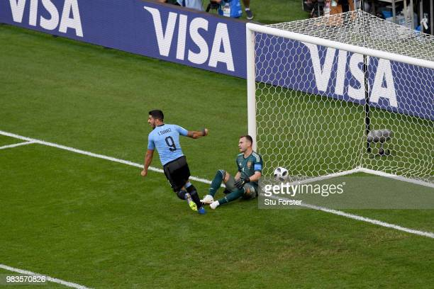 Igor Akinfeev of Russia sits dejected as Luis Suarez celebrates after the second Uruguay goal scored by Diego Laxalt during the 2018 FIFA World Cup...