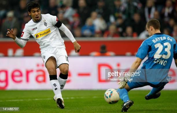 Igor de Camargo of Moenchengladbach and Bernd Leno of Leverkusen battle for the ball during the Bundesliga match between Bayer 04 Leverkusen and...